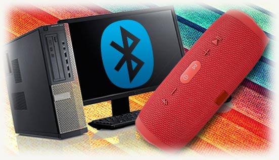 Блютуз колонка на фоне компьютера с логотипом на экране
